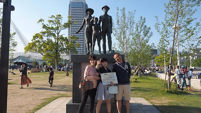像と同じポーズで。1908年に日本からブラジルに初めて移民船が出た記念碑だ。