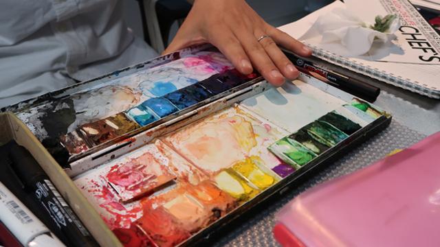 パレットの端に並んでいるさまざまな色は、固まった透明水彩絵の具とのこと。都度水で溶かしながら色をつくっていくのだという