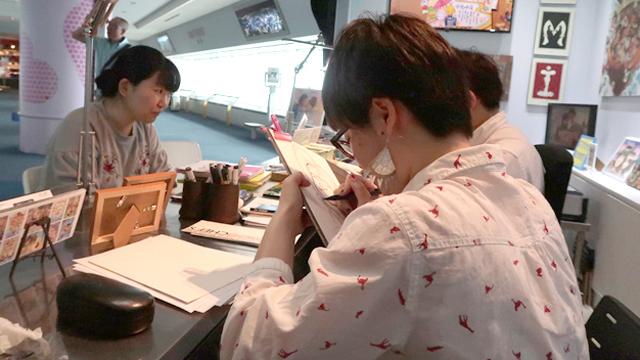 左手で画板をにぎりしめながら、がりがりと描き進めるSAKIさん