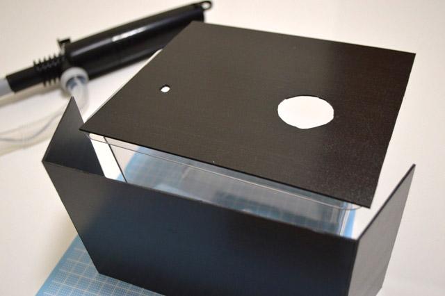 プラ板に灯油ポンプを通すための穴と枡から水をこぼす穴を開ける。またケースが丸見えだとカッコよくないので前面もプラ板で覆った。