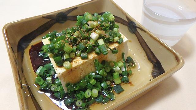 豆腐半丁にゴマ油を大さじ1.5ほど回しかけて、刻んだ小ねぎをお好みでたっぷり乗せたら、そこに醤油を大さじ2ほど回しかける。最後に七味唐辛子を軽く振ってネギ奴の出来上がり。