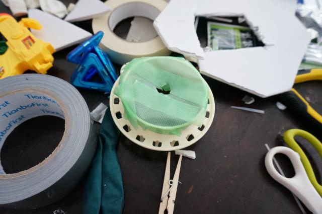 何かのパーツをテープでふさぎ、まんなかに穴をあけたもの。車輪を作ろうとしたのかもしれない