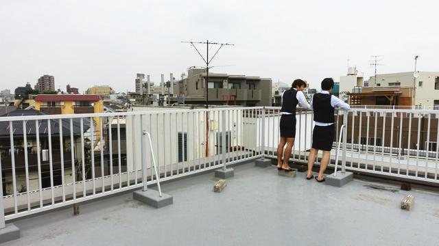 OLと言えば屋上で会話するこういうシーンもドラマだとよく見かける。ちなみにこの写真のポイントは「背が低くて柵に手が届かないOL」を演じるために安藤さんがコンクリートブロックの上に立っているところだ。