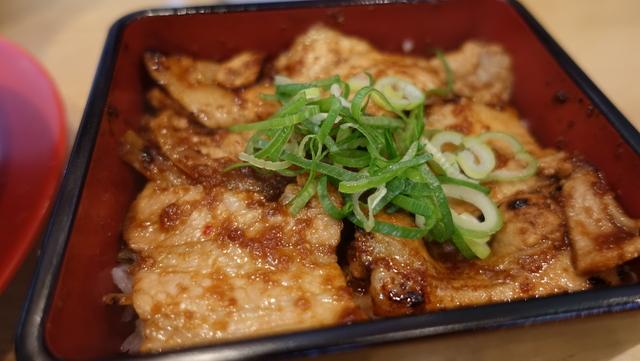 豚重。ご飯の上に敷き詰められ豚ロースにタレがたっぷりとかかっている。