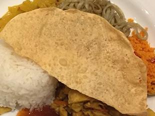 パパダムは南アジアで食べられている薄焼きのクラッカー。細かく砕いてご飯と混ぜる。