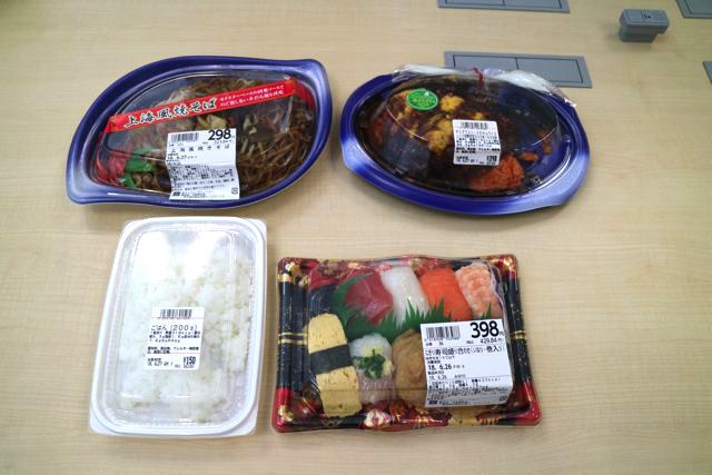 今回はLIFEというスーパーで色々と食べ物を調達した。全員にそれぞれ均等にわけると主食+おかず3品になるくらいの食料を買った。写真は主食となる白飯、寿司 焼きそば、オムライス。主食は数が限られているので、いかに確保するかが今回のゲームの鍵になってくる