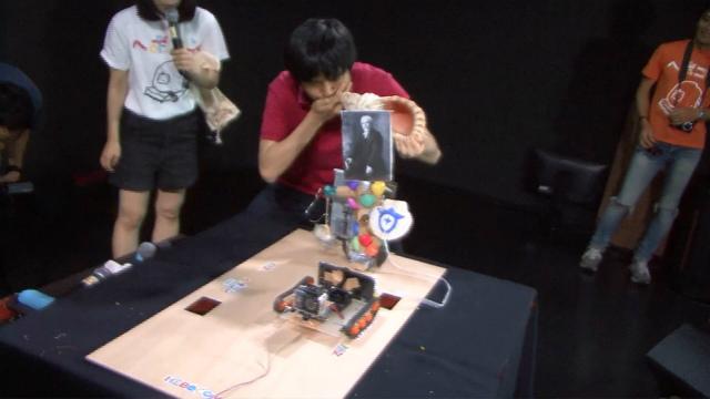 試合開始と同時にほら貝を吹き鳴らす、こやしゅんさん。ほら貝から出る呼気の風力でロボットは動く。
