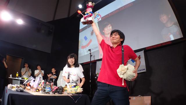 ほら貝を小脇に抱え、賞品の「小学生が作ったトロフィ」を掲げる、こやしゅんさん