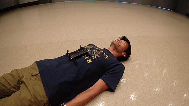 胸にドローンを置かれた安藤さん。そもそも体からドローンは飛ぶのか。