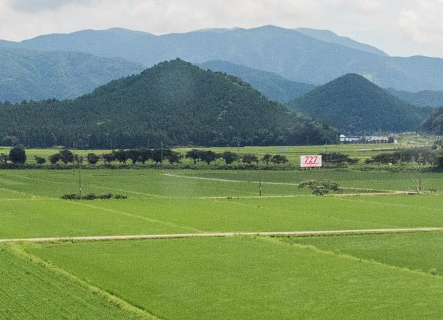 田園風景に鮮やかな「727」の朱。麗しい。背後の山並みとのコントラストがいい。