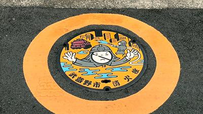 消防士のヘルメットに市章が描かれた武蔵野市の消火栓マンホール