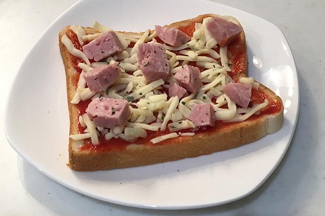 ピザ用チーズ、ボロニアソーセージを切って乗せ、バジルをふりかける