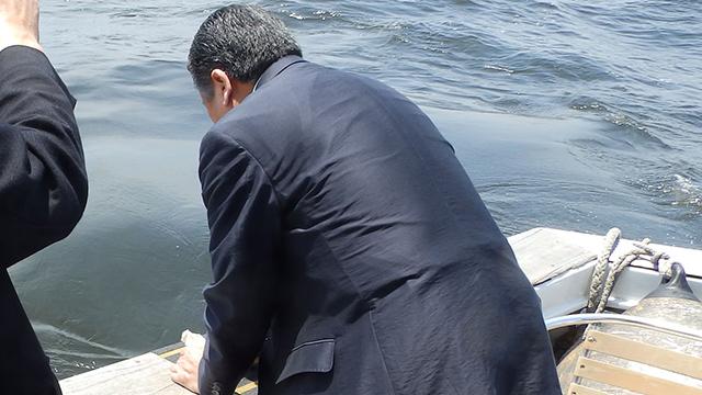 遺骨の入った袋を海へと放つ