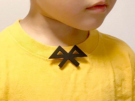 Bluetoothマークをブローチに。モデルは時々登場する息子さん(Photo:大村卓)