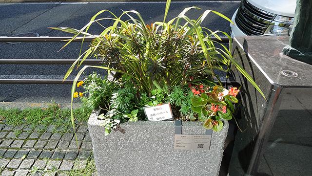 彫刻作品のわきに置いてある公共の園芸